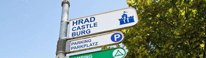 Placas indicando o castelo e o estacionamento em Karlštejn